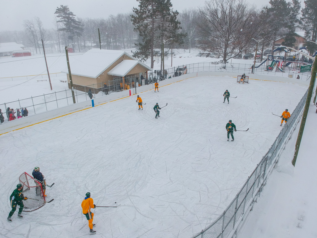 Aerial view of NMU Wildcats playing outdoor hockey match.