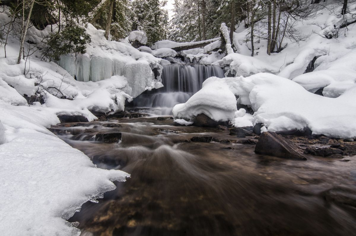 Wagner Falls under a fresh snowfall in Munising, Michigan.